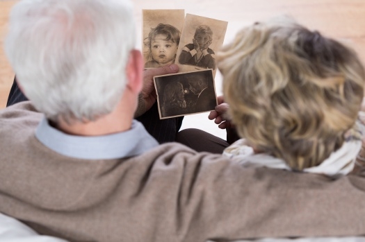 Senior couple looking at old pictures from childhood
